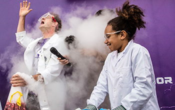 Mad scientist holding a microphone behind a cloud of smoke in between a girl and mad scientist both in lab coats